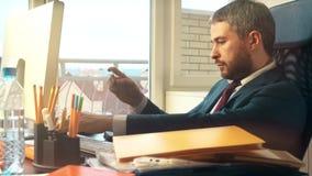Uomo d'affari barbuto bello che effettua pagamento online con la sua carta di credito Fotografia Stock