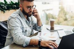 Uomo d'affari barbuto, blogger che si siede in caffè, parlando sullo Smart Phone, lavorante al computer portatile, free lance che fotografia stock