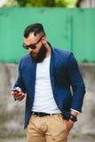Uomo d'affari barbuto che esamina telefono fotografia stock libera da diritti