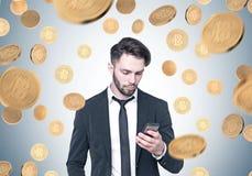 Uomo d'affari barbuto che esamina telefono, pioggia del bitcoin Immagine Stock Libera da Diritti