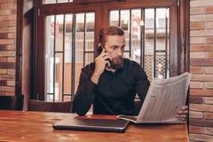 Uomo d'affari barbuto che legge un giornale fotografia stock libera da diritti