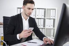 Uomo d'affari barbuto con la battitura a macchina del telefono Fotografia Stock Libera da Diritti