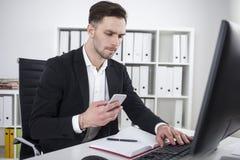 Uomo d'affari barbuto con una battitura a macchina dello smartphone Immagini Stock