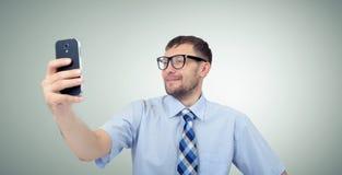 Uomo d'affari barbuto divertente che si fotografa su uno smartphone Fotografie Stock