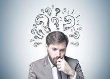 Uomo d'affari barbuto in dubbio, punti interrogativi immagini stock