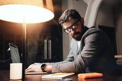 Uomo d'affari barbuto nel funzionamento di vetro dell'occhio dal computer portatile contemporaneo allo studio del collega di nott Immagine Stock