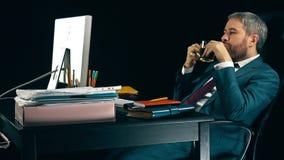 Uomo d'affari barbuto soddisfatto che ha una rottura nel suo luogo di lavoro e che beve tè Priorità bassa nera video 4K stock footage