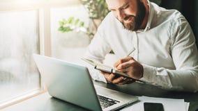 Uomo d'affari barbuto sorridente dei giovani in camicia bianca che si siede allo scrittorio davanti al computer portatile, facent Fotografia Stock Libera da Diritti