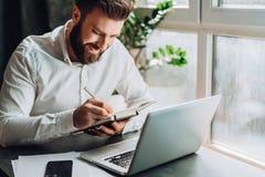 Uomo d'affari barbuto sorridente dei giovani in camicia bianca che si siede allo scrittorio davanti al computer portatile, facent Fotografie Stock