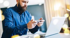 Uomo d'affari barbuto sorridente dei giovani che si siede alla tavola davanti al computer, facendo uso dello smartphone Le free l Fotografia Stock Libera da Diritti