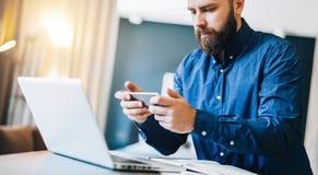 Uomo d'affari barbuto sorridente dei giovani che si siede alla tavola davanti al computer, facendo uso dello smartphone Le free l Fotografia Stock