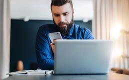 Uomo d'affari barbuto sorridente dei giovani che si siede alla tavola davanti al computer, facendo uso dello smartphone Le free l Immagini Stock