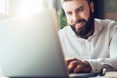 Uomo d'affari barbuto sorridente dei giovani che si siede nell'ufficio alla tavola, facendo uso del computer portatile L'uomo lav Fotografie Stock