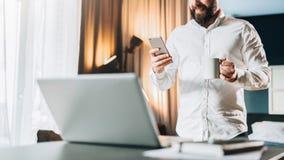 Uomo d'affari barbuto sorridente dei giovani che sta tavola vicina davanti al computer portatile, facendo uso della compressa dig Immagini Stock