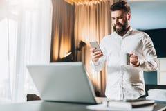 Uomo d'affari barbuto sorridente dei giovani che sta tavola vicina davanti al computer portatile, facendo uso della compressa dig Immagine Stock Libera da Diritti
