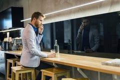 Uomo d'affari bello che beve e che per mezzo del telefono Immagini Stock