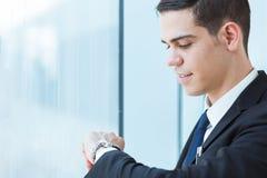 Uomo d'affari bello che esamina il suo orologio fotografia stock