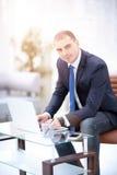Uomo d'affari bello che lavora con il computer portatile in ufficio Fotografia Stock