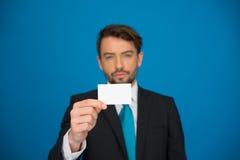 Uomo d'affari bello che mostra biglietto da visita in bianco Fotografie Stock Libere da Diritti