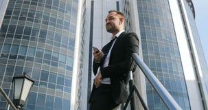 Uomo d'affari bello che parla al telefono Uomo dello Smart Phone che rivolge al telefono cellulare in città Giovane uomo bello di stock footage