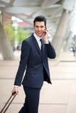 Uomo d'affari bello che parla sul telefono e che cammina all'aperto Fotografia Stock Libera da Diritti