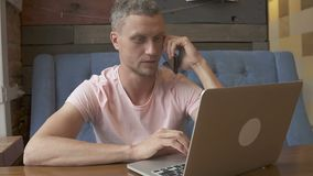 Uomo d'affari bello che parla sul telefono, sorridente mentre lavorando ad un computer portatile stock footage