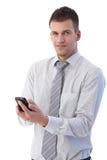 Uomo d'affari bello che per mezzo del telefono mobile Fotografia Stock Libera da Diritti