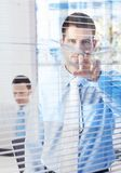 Uomo d'affari bello che pigola attraverso i ciechi Fotografia Stock Libera da Diritti