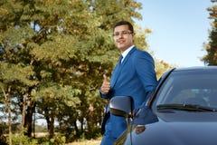Uomo d'affari bello che si appoggia la sua automobile Fotografie Stock