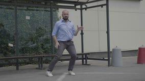 Uomo d'affari bello che si avvia ballando ballo divertente di stile libero mentre è il bus aspettante felice in una stazione pubb video d archivio