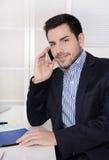 Uomo d'affari bello che si siede allo scrittorio che parla sul cellulare Fotografia Stock
