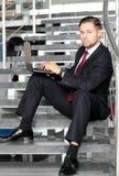 Uomo d'affari bello che si siede sulle scale Immagini Stock Libere da Diritti