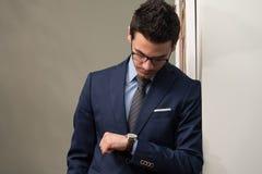 Uomo d'affari bello Checking Time On il suo orologio Fotografia Stock