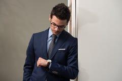 Uomo d'affari bello Checking Time On il suo orologio Fotografie Stock Libere da Diritti