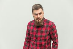 Uomo d'affari bello con i baffi del manubrio e della barba che esaminano macchina fotografica con il fronte arrabbiato fotografie stock libere da diritti