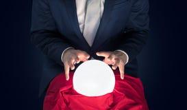 Uomo d'affari bello con la palla magica ed il fondo vuoto scuro fotografia stock libera da diritti