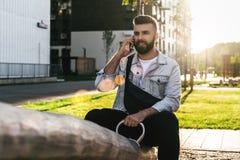 Uomo d'affari bello dei pantaloni a vita bassa con la barba, in rivestimento del denim e seduta e chiamate d'avanguardia di vetro immagine stock libera da diritti