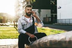 Uomo d'affari bello dei pantaloni a vita bassa con la barba, in rivestimento del denim e seduta e chiamate d'avanguardia di vetro immagine stock
