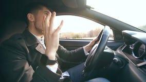 Uomo d'affari bello felice che conduce automobile e che canta L'uomo è felice dopo la fabbricazione degli affari e guida a casa