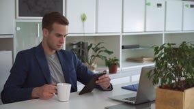 Uomo d'affari bello nella posta moderna della lettura dell'ufficio sulla compressa di tocco video d archivio