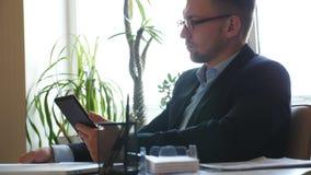 Uomo d'affari bello in occhiali che analizza informazioni di dati statistici su un pc della compressa in ufficio Giovane imprendi archivi video