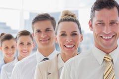 Uomo d'affari bello sorridente che sta con il suo gruppo Immagini Stock