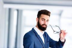 Uomo d'affari bello Taking Off Eyeglasses immagine stock