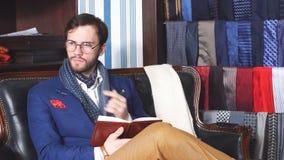 Uomo d'affari bello in un vestito di classe che ha un umore di ispirazione che fa alcune note, mentre sedendosi sul sofà d'annata archivi video