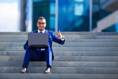 Uomo d'affari bello in vestito ed occhiali che si siedono con il computer portatile immagine stock libera da diritti