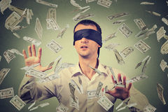 Uomo d'affari bendato che prova a prendere le banconote delle banconote in dollari che volano in aria Fotografia Stock
