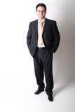 Uomo d'affari bianco diritto sorridente in vestito con le mani in caselle Fotografia Stock