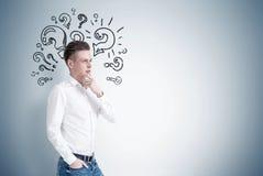 Uomo d'affari biondo pensieroso, punti interrogativi Fotografia Stock