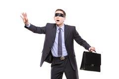 Uomo d'affari blindfold confuso con la cartella fotografie stock