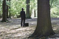 Uomo d'affari With Briefcase Standing in foresta immagine stock
